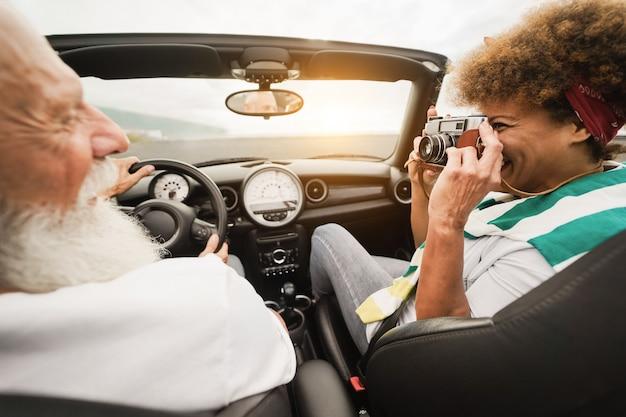 Gelukkige senior paar plezier in converteerbare auto tijdens zomervakantie - belangrijkste focus op vintage camera