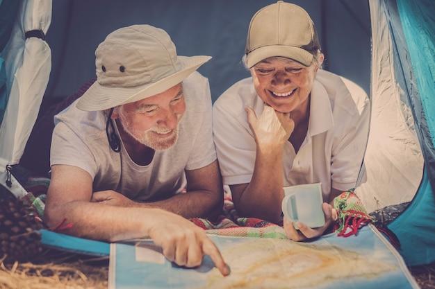 Gelukkige senior reizigers die samen op zoek zijn naar een papieren kaart om de volgende vakantiebestemming te kiezen