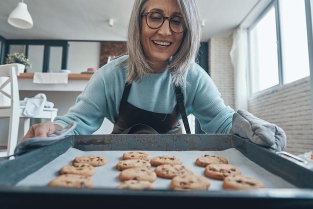 Gelukkige senior vrouw die lacht tijdens het bereiden van koekjes in de keuken