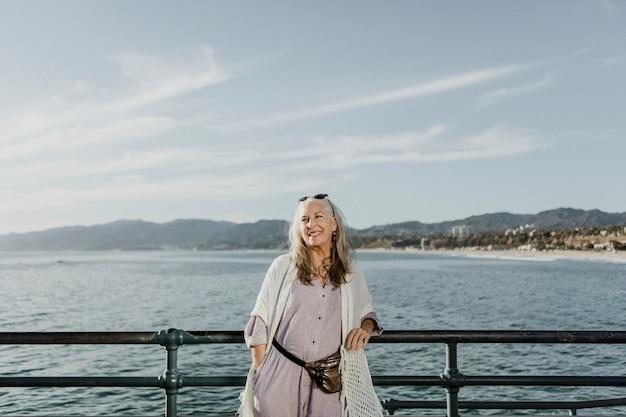 Gelukkige senior vrouw die op de pier staat