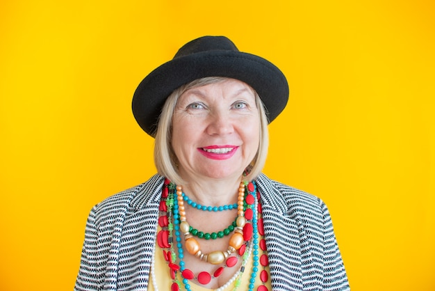 Gelukkige senior vrouw die plezier heeft in stijlvolle kledingconcepten over senioren