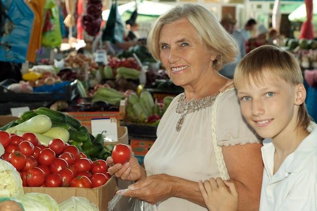 Gelukkige senior vrouw met jongen op markt f, boodschappen kiezen
