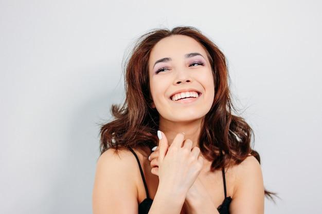 Gelukkige sensuele glimlachende meisjes aziatische jonge vrouw met donker lang krullend haar