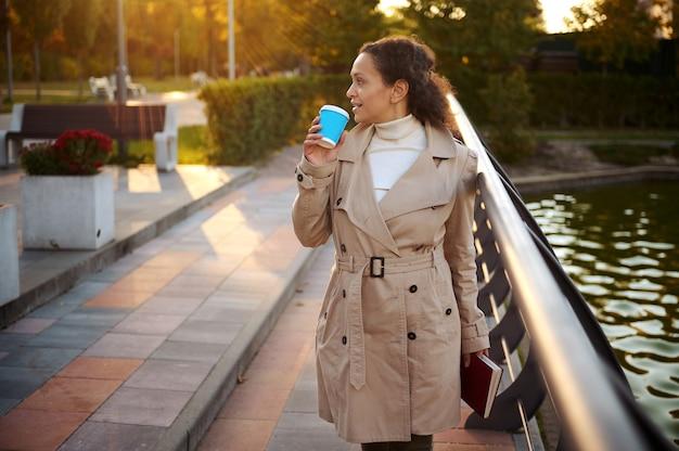 Gelukkige serene vrouw loopt door het park, houdt een boek vast en drinkt koffie, geniet van haar herfstweekend in mooie warme zonnige dat bij zonsondergang op de achtergrond van gele herfstnatuur