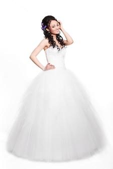 Gelukkige sexy mooie bruid donkerbruine vrouw in witte huwelijkskleding met kapsel en heldere make-up volledige lengte in retro stijl