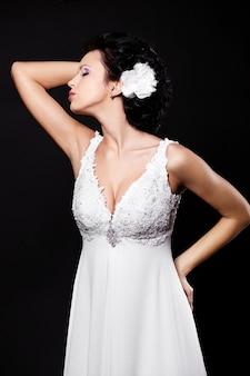Gelukkige sexy mooie bruid donkerbruine vrouw in witte huwelijkskleding met kapsel en heldere make-up