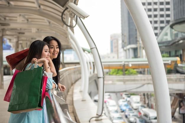 Gelukkige shopaholic aziatische jonge vrouwelijke vrienden houden winkelpapieren tassen vast en zoeken in de winter naar een winkelcentrum in de stad. twee lachende vrouwen genieten van kortingsverkoop in de moderne stad. buitenlandse reizigers.