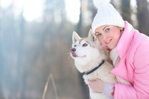 Gelukkige siberische husky met eigenaar op wandeling in winterpark