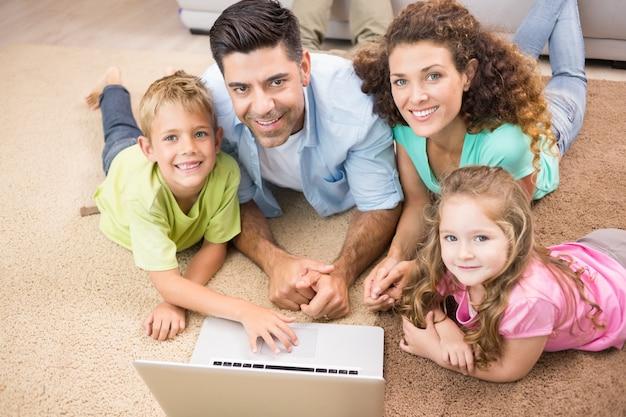 Gelukkige siblings die op de deken liggen die laptop met hun ouders met behulp van