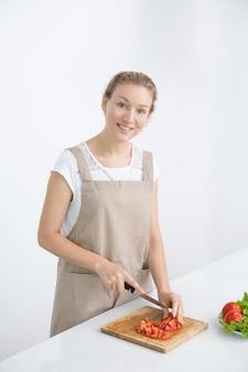 Gelukkige slanke vrouw die vegetarische salade koken