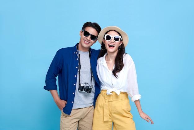 Gelukkige speelse aziatische paartoerist gekleed in zomerkleren om op vakantie te reizen die op blauwe achtergrond wordt geïsoleerd.