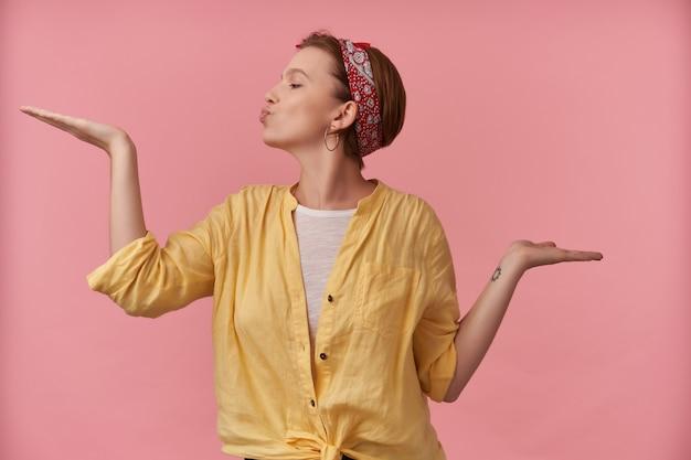 Gelukkige speelse jonge vrouw in geel overhemd met hoofdband op hoofd die lege ruimte op beide handpalmen houdt en een kus over roze muur verzendt