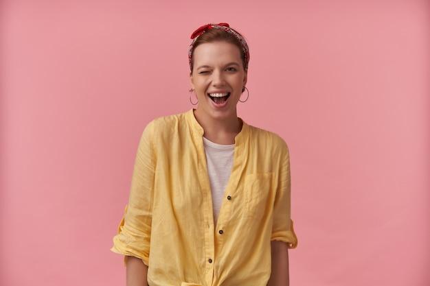 Gelukkige speelse jonge vrouw in geel overhemd met rode hoofdband op hoofd die flirt en over roze muur knipoogt