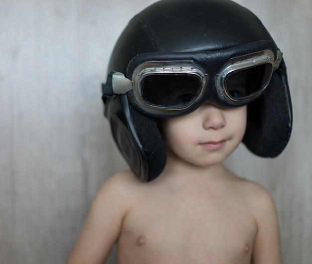 Gelukkige speelse kleine jongen met vliegende helm