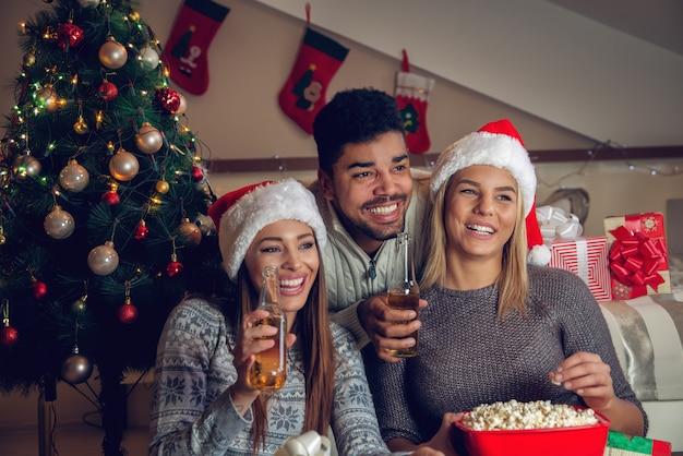 Gelukkige speelse mooie kerstvrienden met kerstmutsen