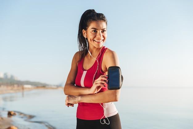 Gelukkige sportenvrouw die zich voorbereiden te rennen en wegkijken