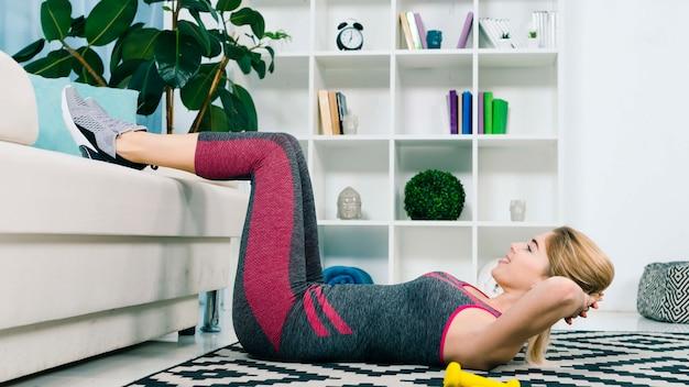 Gelukkige sportieve jonge vrouw die geschiktheidsoefening in de woonkamer doet