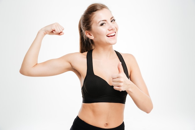 Gelukkige sportieve vrouw die ok teken en geïsoleerde biceps toont