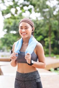 Gelukkige sportieve vrouw met gadget in park