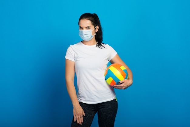 Gelukkige sportieve vrouw met gezichtsmasker van de bal van de coronavirusholding. geïsoleerd op blauw