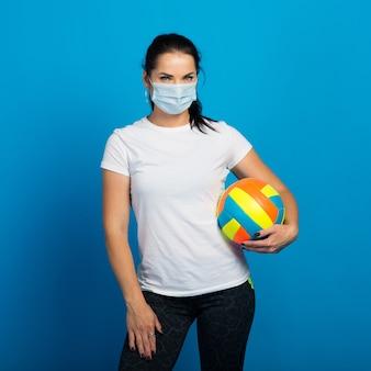 Gelukkige sportieve vrouw met gezichtsmasker van de bal van de coronavirusholding