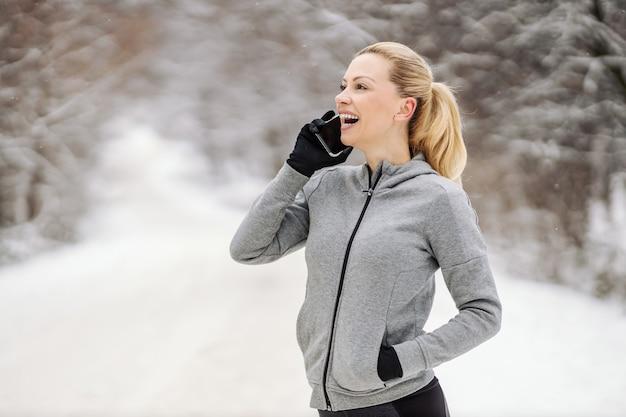 Gelukkige sportvrouw die een pauze neemt van oefeningen en een telefoontje heeft terwijl hij in de natuur staat op een besneeuwde winterdag.