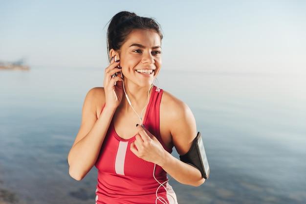 Gelukkige sportvrouw die muziek luistert en weg kijkt