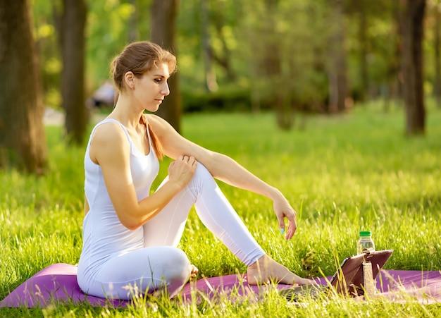 Gelukkige sportvrouw die online yogaoefening op laptop bekijkt.