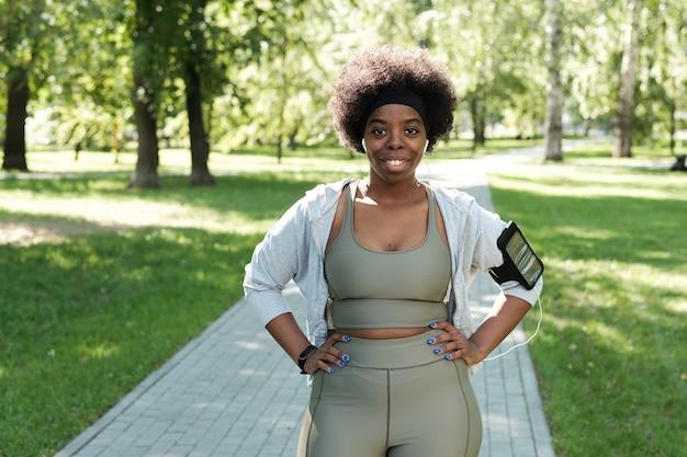 Gelukkige sportvrouw met grote maten die in het park staat