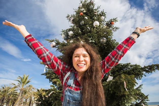 Gelukkige springende vrouw over kerstboomachtergrond