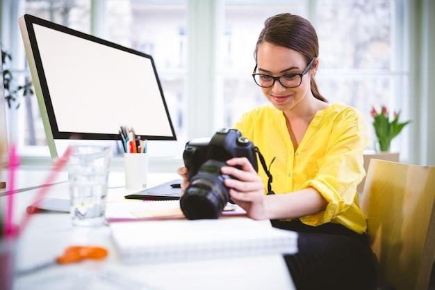 Gelukkige stafmedewerker die camera in creatief bureau bekijkt