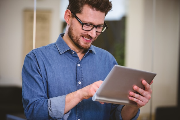 Gelukkige stafmedewerker die digitale tablet gebruiken op creatief kantoor