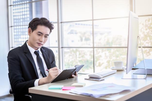 Gelukkige stemming een vrolijke aziatische jonge zakenman heeft ideeën, maak een notitie van het succesvolle businessplan in een notebook en computer op een houten tafelachtergrond op kantoor.