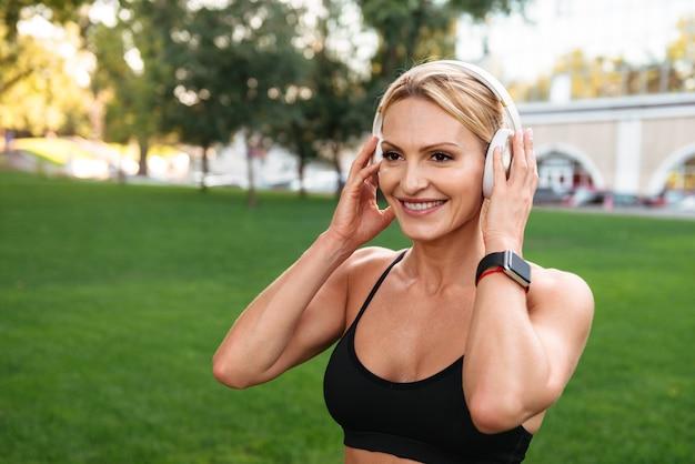 Gelukkige sterke jonge sportenvrouw die in openlucht muziek luistert