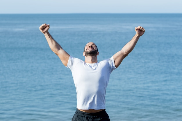 Gelukkige sterke man vieren sport succes op zee
