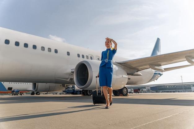 Gelukkige stewardess die buiten loopt en koffer vasthoudt