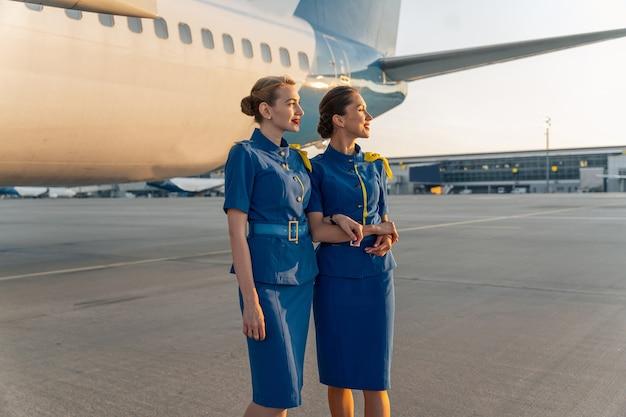 Gelukkige stewardessen poseren tegen de achtergrond van een vliegtuig voor de vlucht