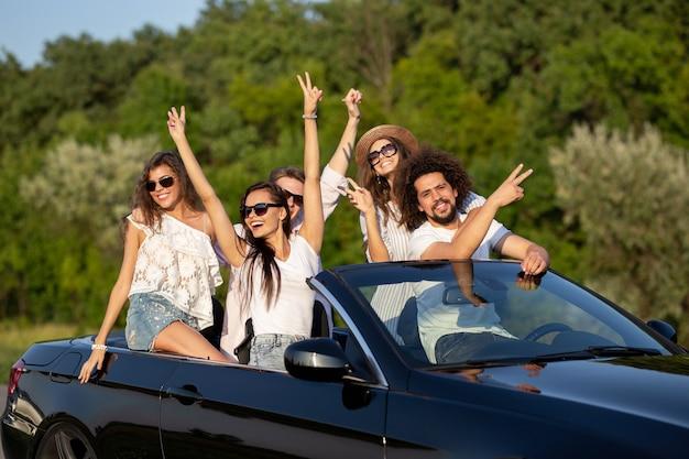 Gelukkige stijlvolle jonge donkerharige meisjes en jongens in zonnebrillen glimlachen in een zwarte cabriolet op de weg en houden hun handen omhoog op een zonnige dag. .