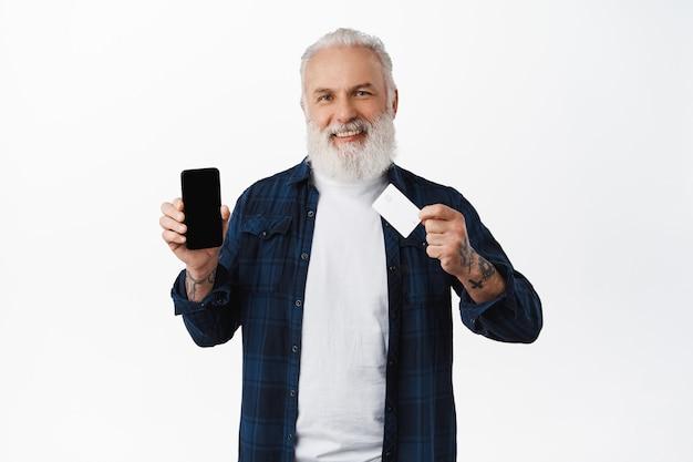 Gelukkige stijlvolle oude man die het scherm van de mobiele telefoon en creditcard toont, tevreden glimlacht, toepassing op smartphone aanbeveelt voor betaling, online betaalt, over witte muur staat