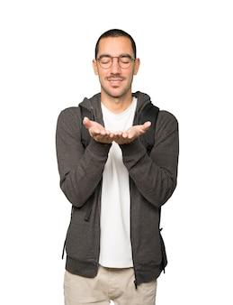 Gelukkige student die iets met zijn hand houdt