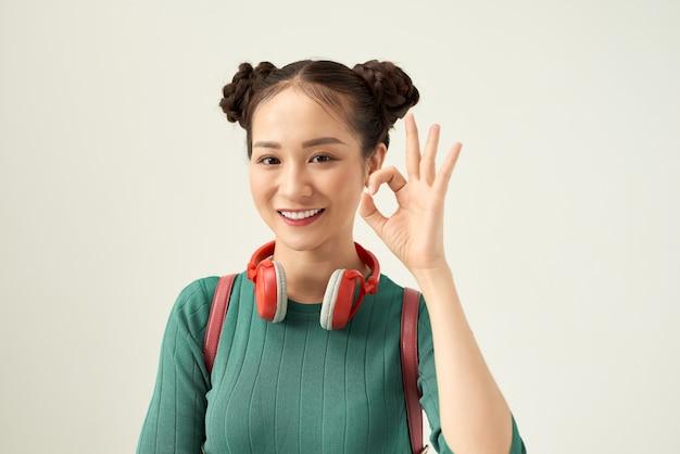 Gelukkige student die oke gebaar toont terwijl het glimlachen bij camera die op wit wordt geïsoleerd