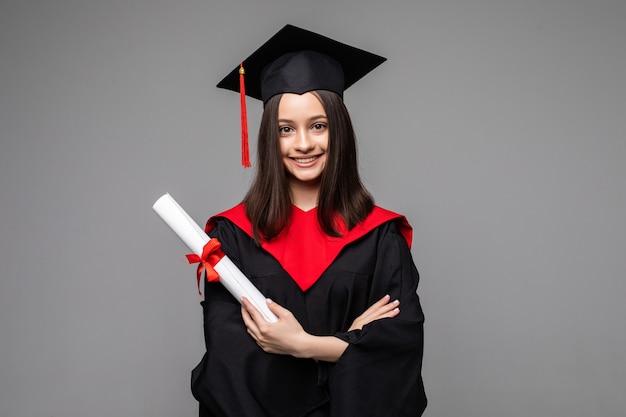 Gelukkige student met afstudeerhoed en diploma op grijs
