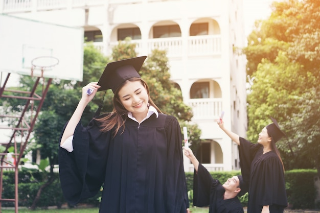 Gelukkige student met diploma met vrienden achter. celebrating succes, onderwijs doel concept.