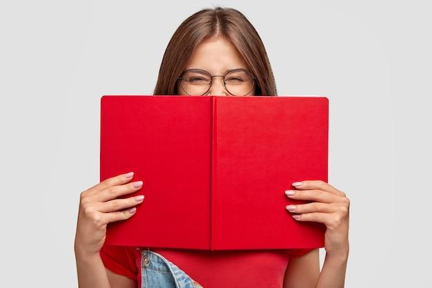 Gelukkige studente lacht positief, draagt een ronde bril, verstopt zich achter een rood boek, glimlacht als iets grappigs leest, poseert tegen een witte muur. mensen, jeugd, onderwijs en lezen concept