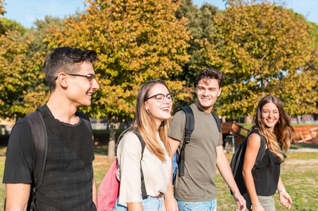 Gelukkige studenten bij park dat en pret glimlacht heeft