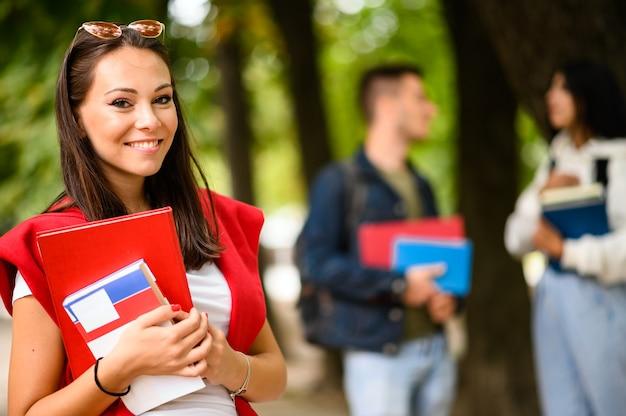 Gelukkige studenten die buiten in een park glimlachen