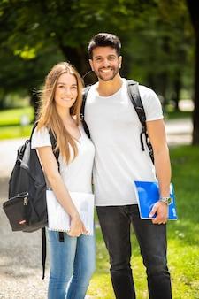 Gelukkige studenten die buiten in een warme zonnige dag glimlachen