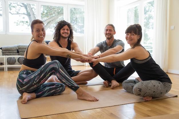 Gelukkige studenten die handen samen na yogaklasse houden