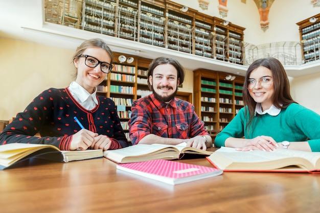 Gelukkige studenten die in de bibliotheek schrijven