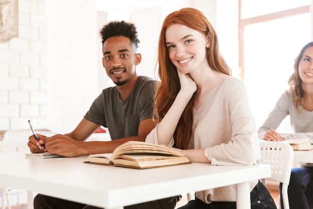 Gelukkige studenten die in de klas zitten